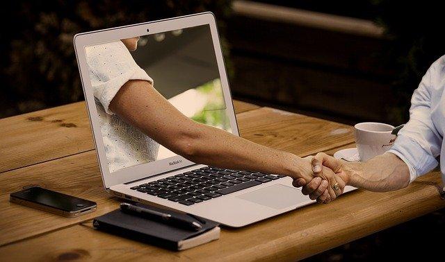 PCと握手の画像
